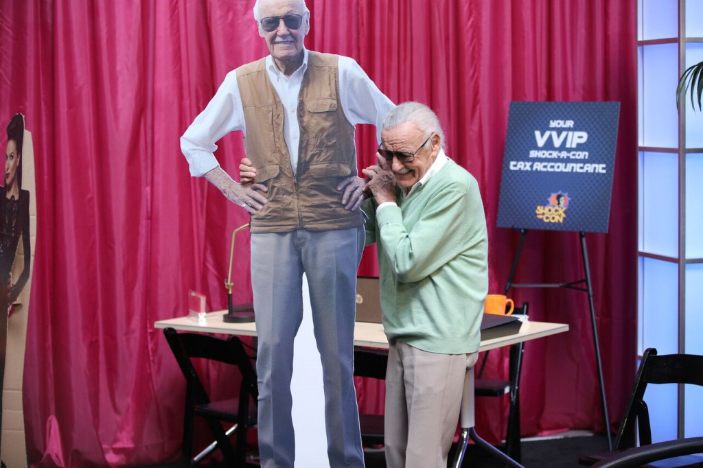 "Stan Lee (as himself) holding a cardboard cutout of himself on ""Con Man"" season 2. (Comic-Con HQ.)"