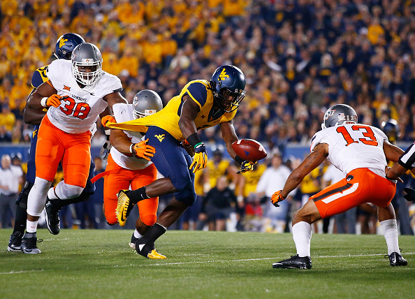 MORGANTOWN, WV - OCTOBER 10:  Rushel Shell #7 of the West Virginia Mountaineers fumbles the ball before it is recovered by Jordan Sterns #13 of the Oklahoma State Cowboys in the first half during the game at Mountaineer Field on October 10, 2015 in Morgantown, West Virginia.  (Photo by Jared Wickerham/Getty Images)
